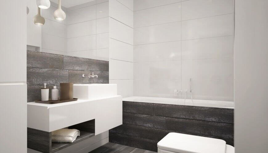 Weathered grey wood counterbalances the use of white in this striking bathroom. The angular vanity/sink area, tub, and toilet mimic the square angles of the tiled walls.