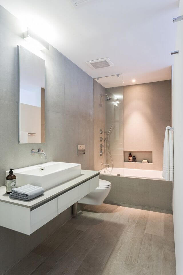 This narrow bathroom maintains a muted palette to help the space feel larger than it really is. White accents - including the white accent wall - help to reflect more light, brightening up the entire room.