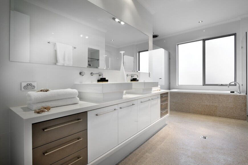 This strikingly designed bathroom uses a light, sand colored floor to offset the white decor. Raised sinks break up the long vanity top, a glass enclosed shower can be seen in the corner of the room near the tub.