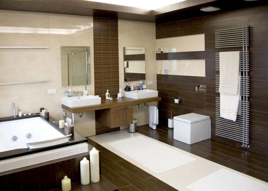 Bright white accents complement the dark brown tones of the wood used in this bathroom. The freestanding square sinks match the square angles of the soaking tub and the toilet seen on the far side of the bathroom.