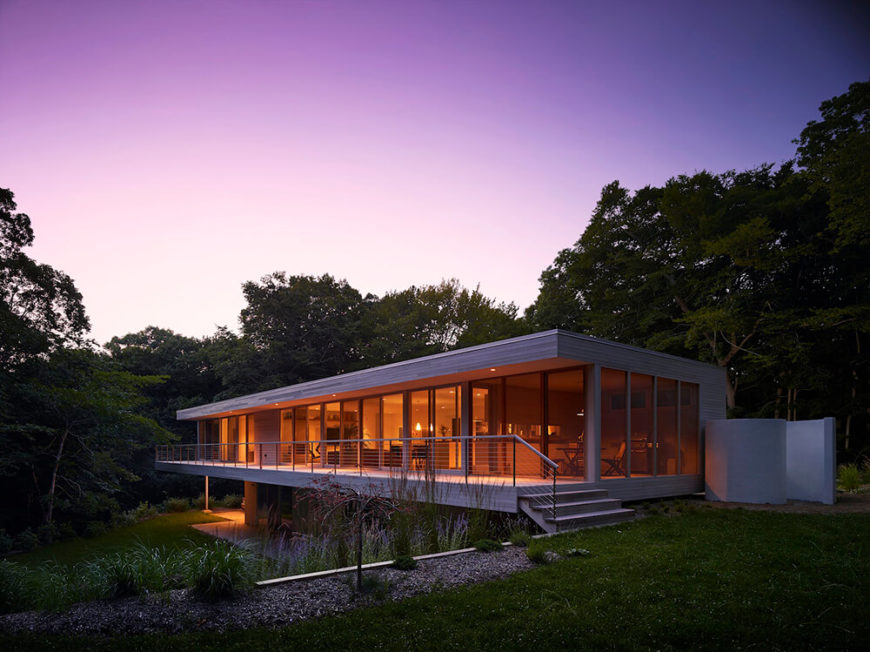 At dusk, we see the interior lit up from end to end through the structure-wide expanse of glass panels. The house is truly meshed with its environment while standing out in sharp contrast.
