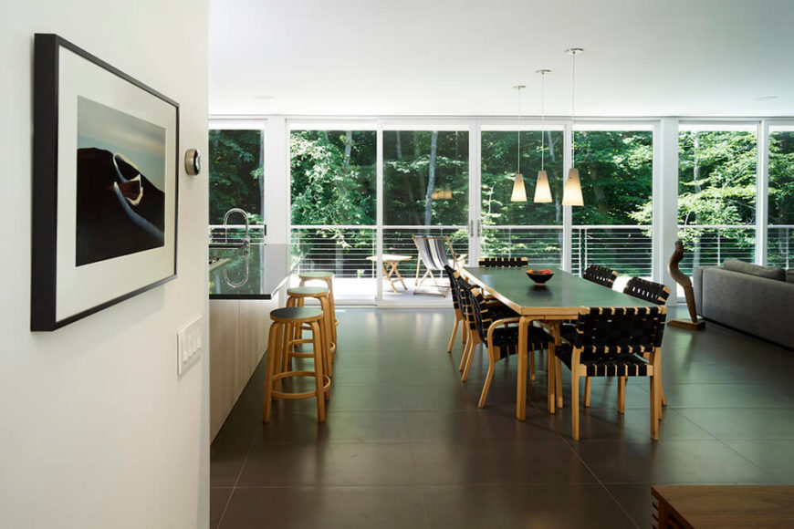 The dining area holds a lengthy natural wood table and set of chairs, upholstered in black with matching black tabletop. Beyond, we see the expansive balcony with the treeline behind it.
