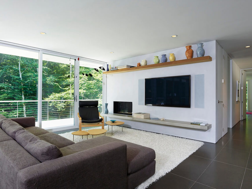 The living room area centers on a white shag rug, contrasting with the large format grey tile flooring seen throughout the interior. Natural wood and stone shelving bracket the entertainment wall, while modern furniture completes the look.