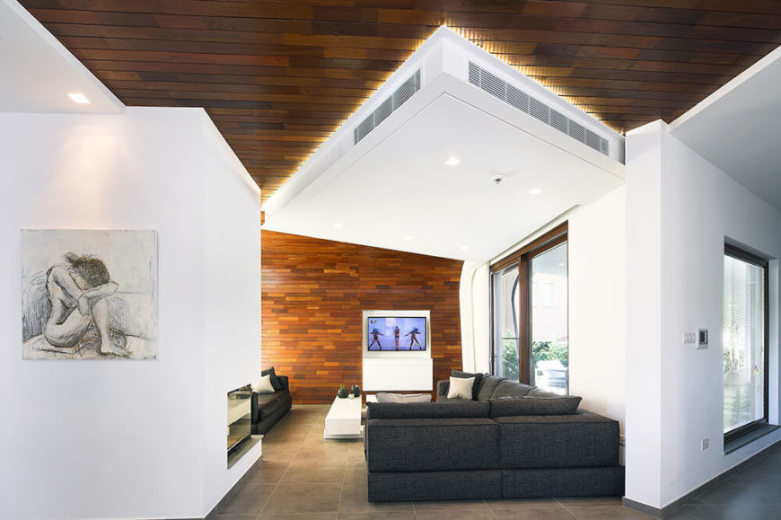 The center of the home is an open-plan area that is defined by the contrast between white walls and rich wood paneling. A large ventilation unit is tucked against the ceiling here, hovering over the living room.