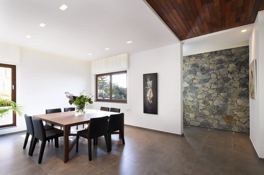 Turning left, we see the grand dining room space near the front entry. A large natural wood table stands surrounded by black leather upholstered chairs, contrasting nicely with the bright walls.