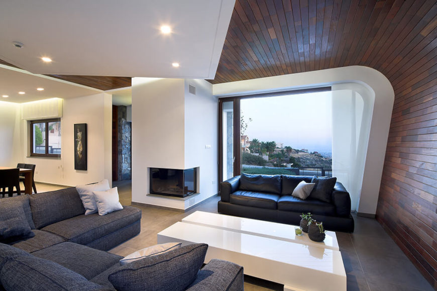From the living room, we can see over the city and down to the harbor via the massive sliding glass panel that frames the front wall. The glass enclosed fireplace at left helps define the entryway as well.