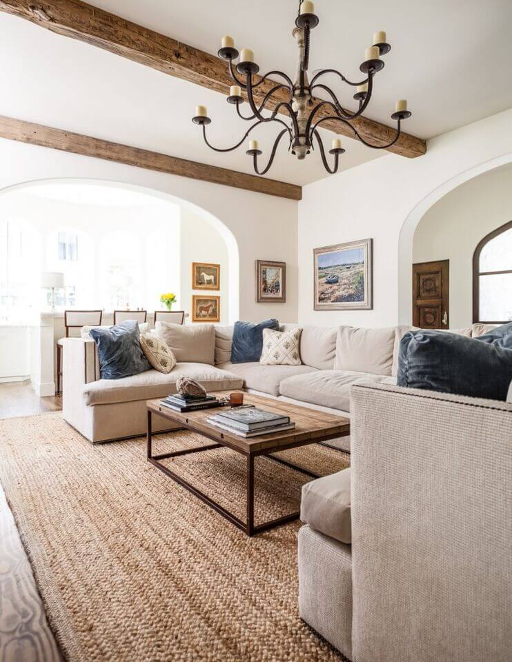 Here's a more contemporary living room design, with white walls, hardwood flooring, and wide arch entries. The white ceiling features the high contrast appearance of rich natural wood exposed beams.