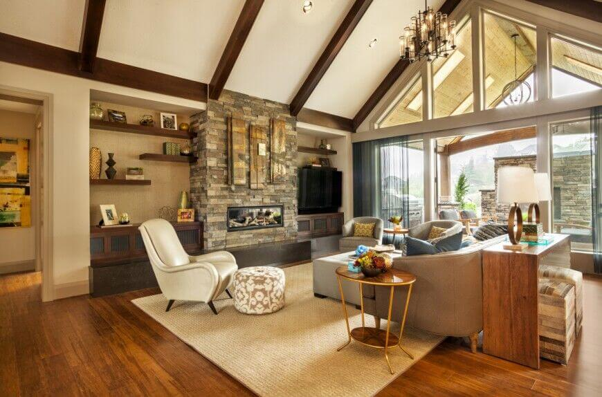 Here's another great vaulted ceiling in white, with dark wood exposed beams for contrast. The rich furnishings of the living room stand in natural light, courtesy of full height windows.