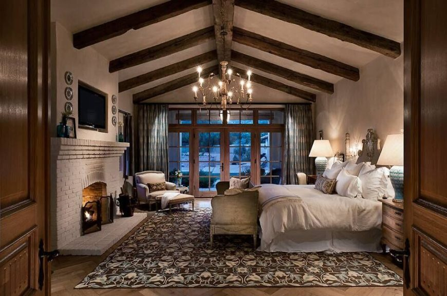 This gorgeous master bedroom has high ceiling with stunning rustic wood work. It's egg shell white old brick fireplace has a cozy television nestled into the wall above it.