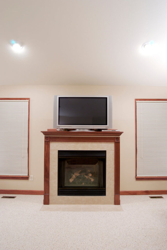 This fireplace combines two different types of materials with a tile hearth and a wooden mantle for a subtle contrast. The TV can sit directly on top of the large mantle without unbalancing the room.