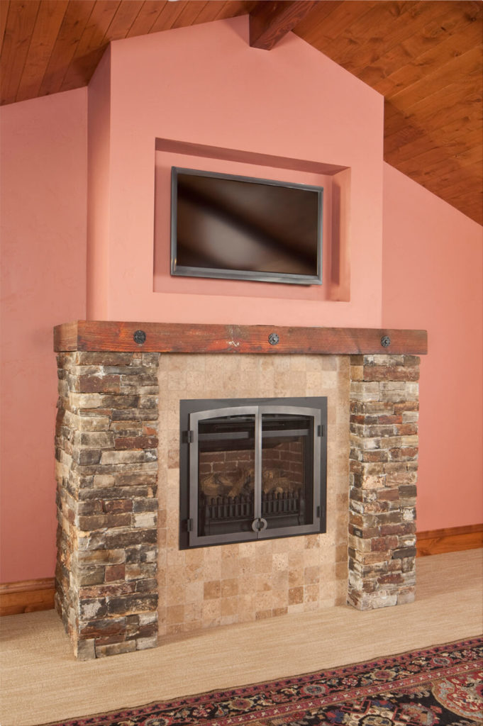 This old fashion fireplace adds modern and traditional looks together. The rustic stone work and the flat screen TV work together for a delicate combination of styles.
