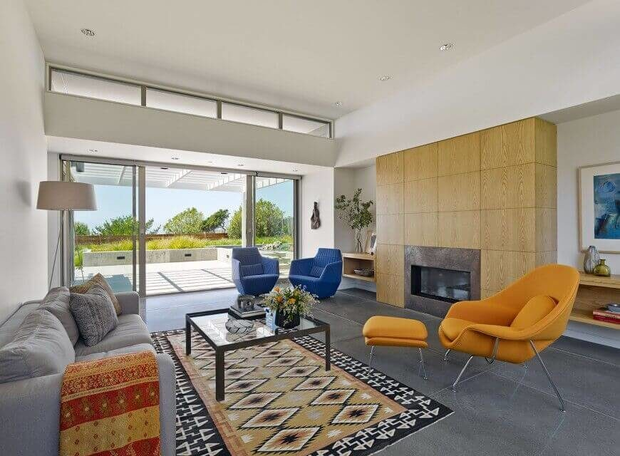 Seamless sliding doors in addition to a set of windows at the top of the ceiling ensure that this living room gets plenty of light.