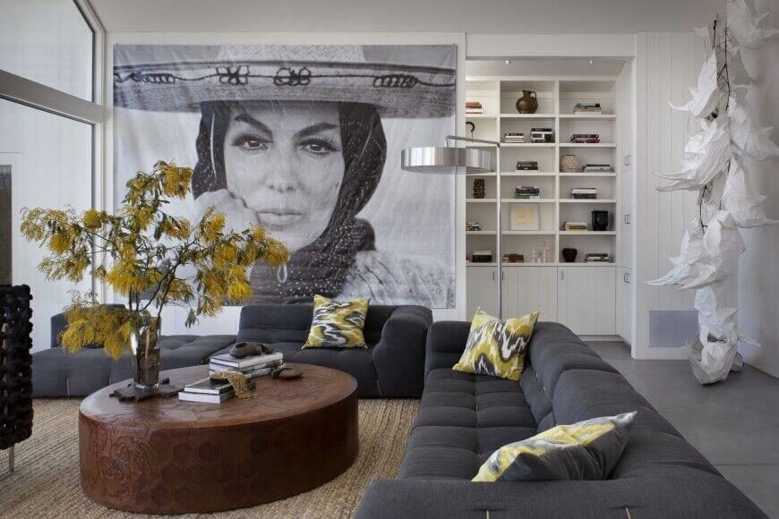 An enormous print takes up almost an entire wall, drawing attention from the solid charcoal gray sectional sofa. Light greens add a pop of color.
