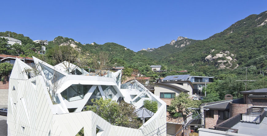 Glancing across the intricately angled rooftop toward the surrounding mountains, we can see how the shape of the home closely mirrors the landscape. The stark contrast of its sleek white panels and living roof makes for a striking appearance.