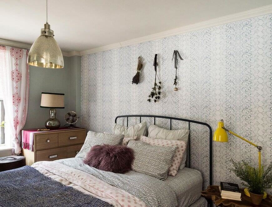 This room features a design that focuses on detailed patterns, creating a unique visual effect. The bright yellow lamp and dark colored accent pillow contrasts the detailed theme and balances the rest of the space.