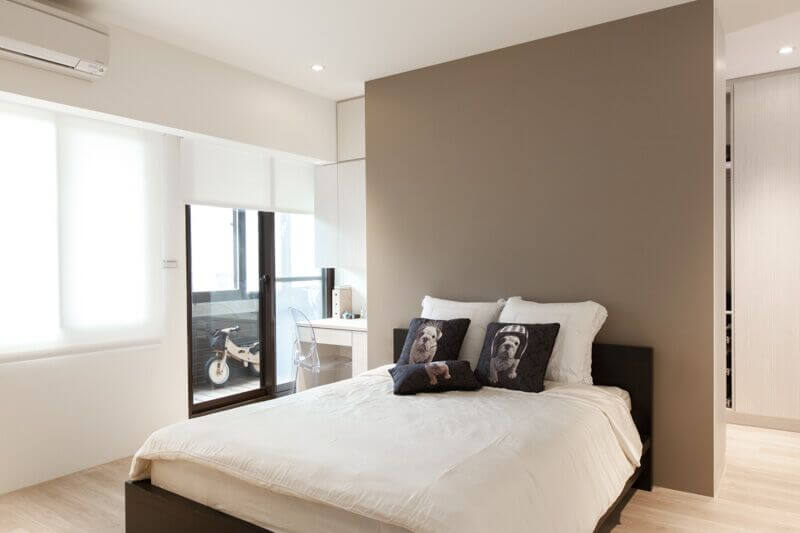 A simple bedroom with neutral colors, and a bed centered in the space. The accent pillows give the room its character, and the bed itself is framed by the darker accent wall. A wall of windows lets natural light flood into the room.