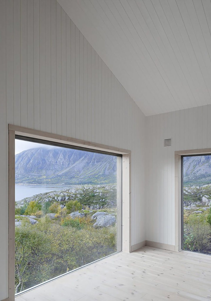 Viewing the corner of the living room, emptied of furniture, we can appreciate the clean lines and warm tone of the white walls and rich natural wood. We can also appreciate the vast landscape unfurling beyond the windows.