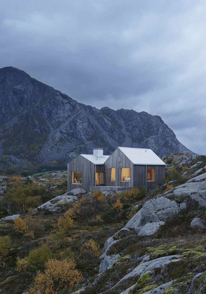 As the rocky landscape cascades down this slope, the home itself emerges organically, with a color palette that blends in perfectly with the environment. Large windows offer expansive views of the surroundings.