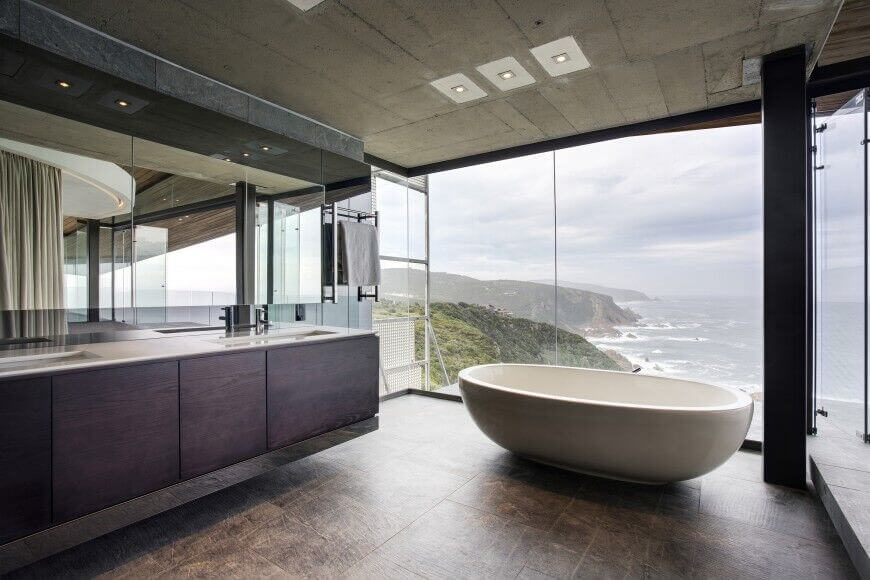 this bathroom space features floor to ceiling windows which let in plenty of natural light