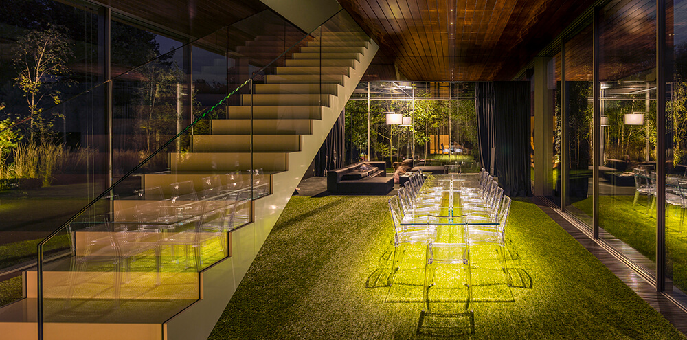 Marvelous dining room that can give you a feel of an al fresco dining. It has a glass table and chairs sitting on the faux grass carpet.