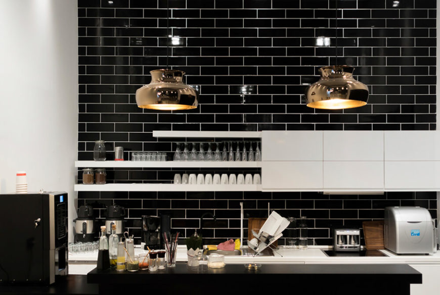 These shiny brass lights make a stunning statement against the black subway tile of this monochromatic kitchen. Golden light reflects from the insides of the pendant lights and warms up the stark kitchen colors.