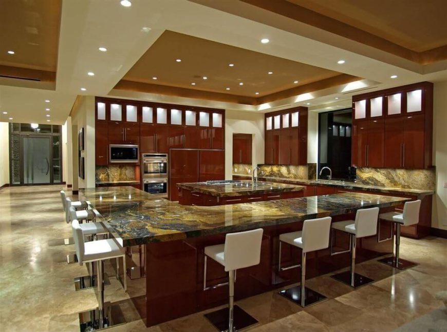Small can lights are recessed into the recessed ceiling, which in turn is surrounded by bars of recessed lighting creating both a subtle ambient glow and pools of bright white light around the room. The spotlights show off the gorgeous granite, as well as lighting up the surfaces used for working and eating.