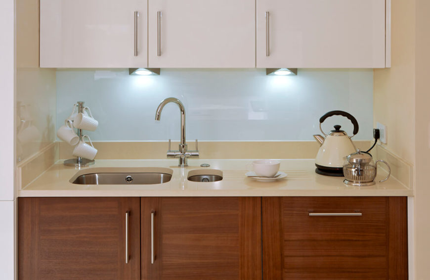 These uniquely shaped spotlights do a great job of lighting up the countertop of this little tea corner with soft, white light. The glossy white backsplash helps to diffuse reflected light around the space as well.