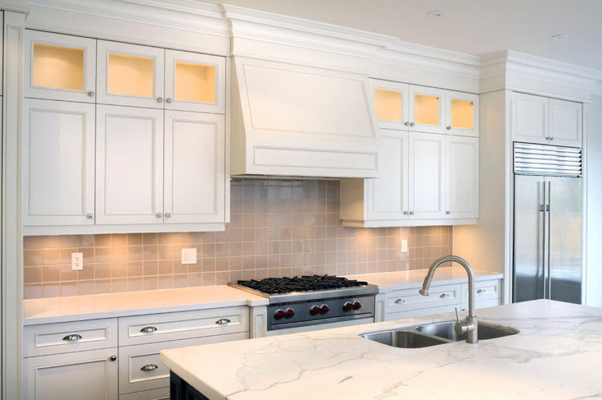 These little spotlights add a subtle glow to the counter space for better lighting. The upper cabinets, with their backlit glass doors, make for a great place to display collectibles or fancy kitchen pieces.