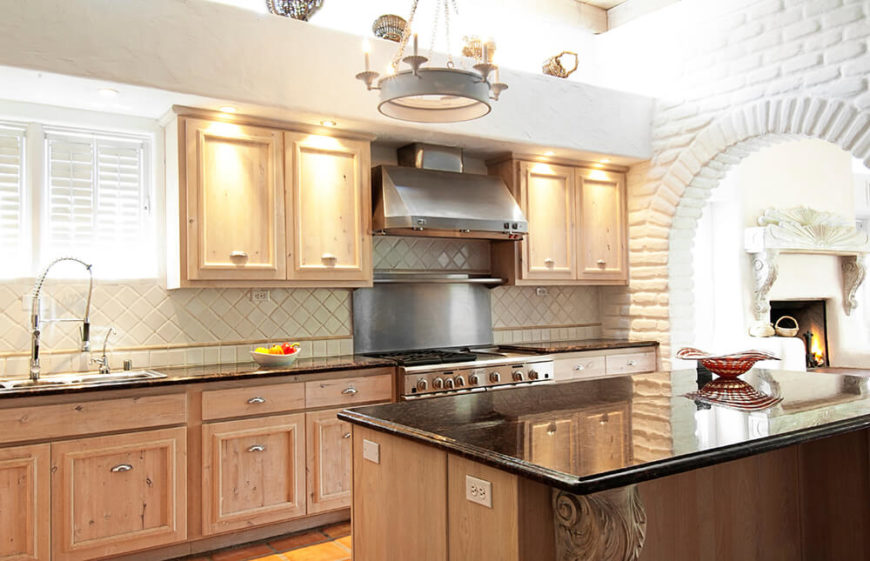 These above-cabinet lights create a highlight for the lovely natural wood cabinets that take centerstage in this kitchen. The puddles of light also brighten up the granite counters - showing off the flecks of color in them.