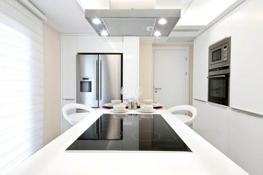 The four small, but bright, spotlights in this stove hood ensure that the cooktop is well lit and the small breakfast bar of the island is lit as well. The impressive amount of white in this kitchen reflects so much from the recessed lighting in the ceiling that the stove hood lights are only necessary for the cooktop.