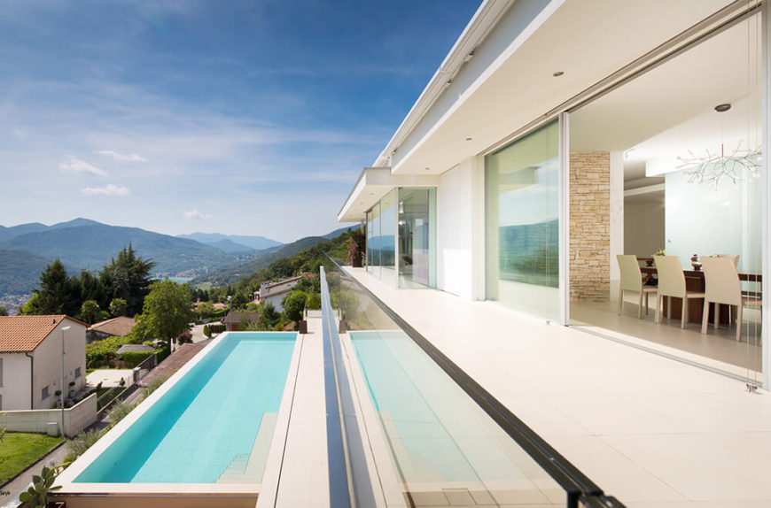 This side of the home is almost entirely glass, offering expansive views over the cascading landscape. The sleek surfaces and glass balustrade make for a brilliant transition from the interior to the pool.