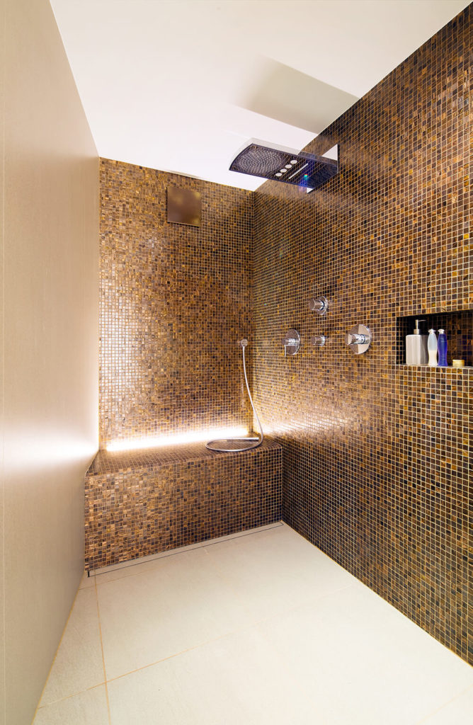 The walk in shower is a large space highlighted by intricate tile walls and recessed lighting. A rainfall shower head punctuates the space with an ultra modern touch.