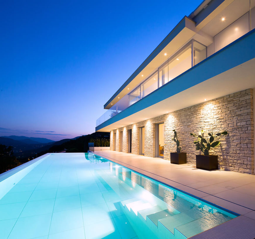 The lower level is more closed off than the top floor, but features multiple openings to the patio and pool area. The pool itself features an infinity edge for seamless views over the landscape.