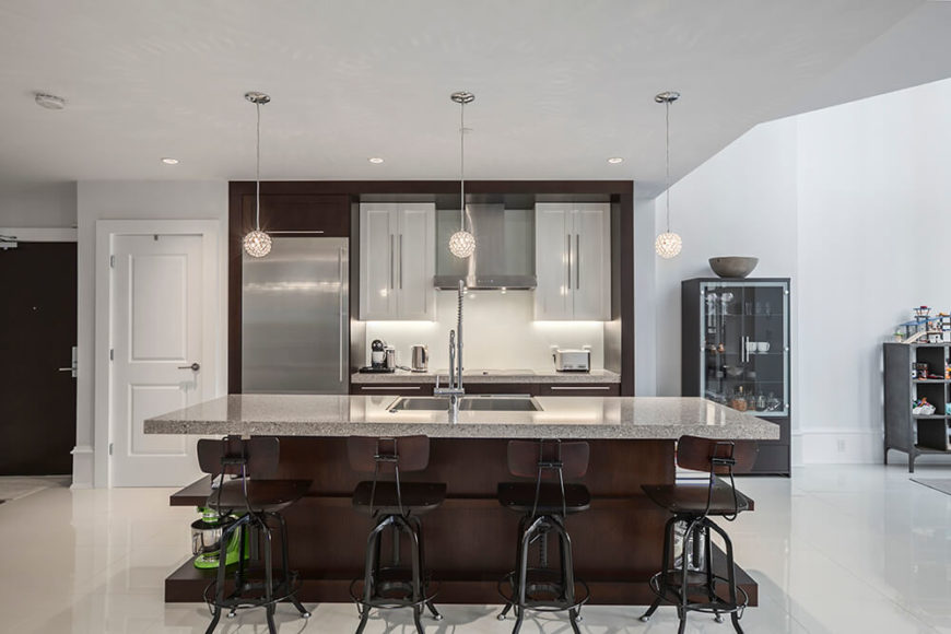 The kitchen flaunts incredible colors and materials of all different types. From stainless steel appliances, to chocolate wooden furniture, to ebony-gray granite countertops.