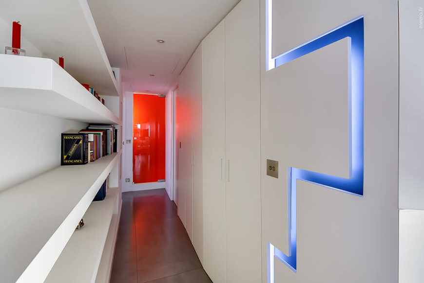 The dark floor tiles lead down a hallway towards a glistening red door. A unique blue geometric bolt slices through the flawless white walls for a unique addition of light.