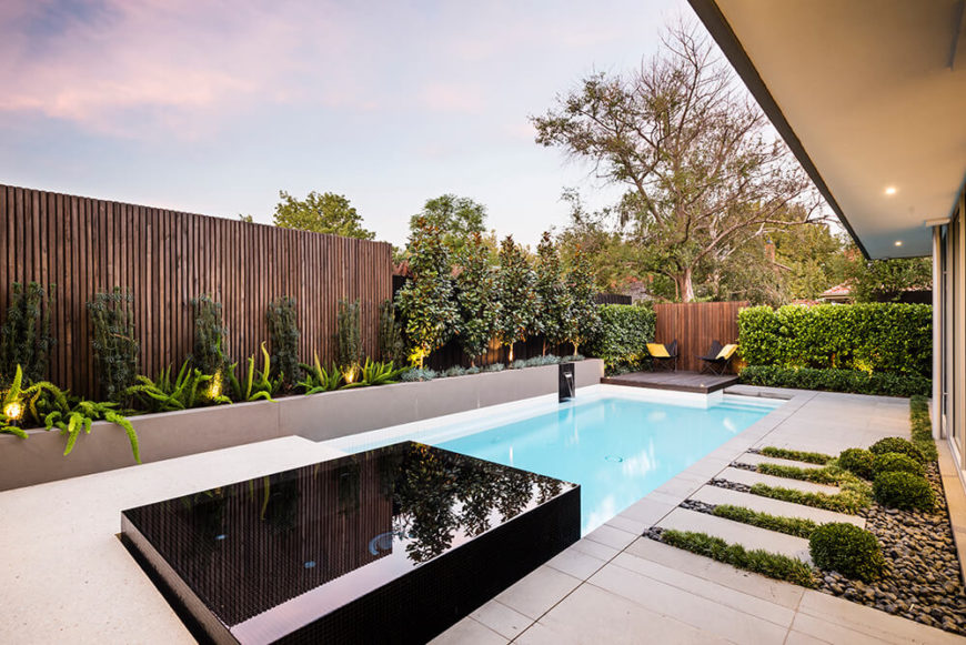 The charcoal planter box runs the length of the pool and creates a visually interesting contrast to the pale waters of the pool and white terrazzo slab. The selection of plants creates an interesting a lively palette in the back patio.