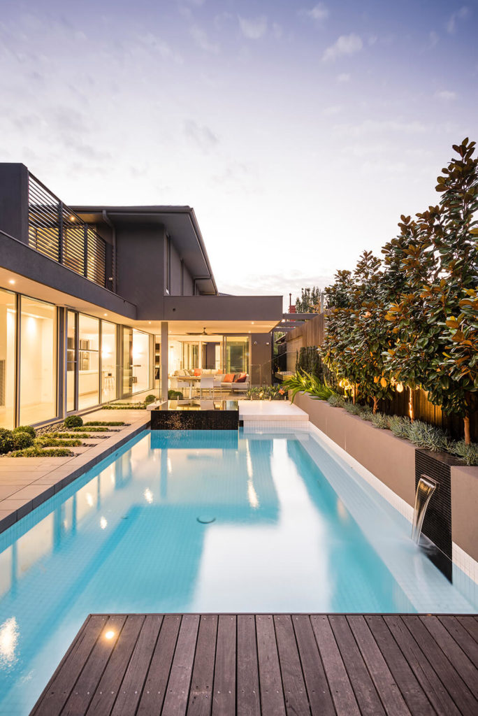 A timber sun deck frames the eastern edge of the pool are and gives added functionality to the space. Up the side of the pool a strip of mosaic tiles wrap up and over the wall. Within this strip a stainless steel C channel acts as a water feature for the pool.