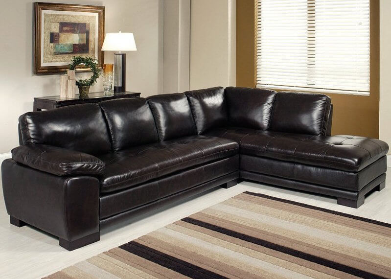The bulging, rich leather cushions are the first element that stands out on this broad and beautiful dark sectional. The chaise lounge and standard sofa halves share a thick button tufted seat design that stands over a broad hardwood base.