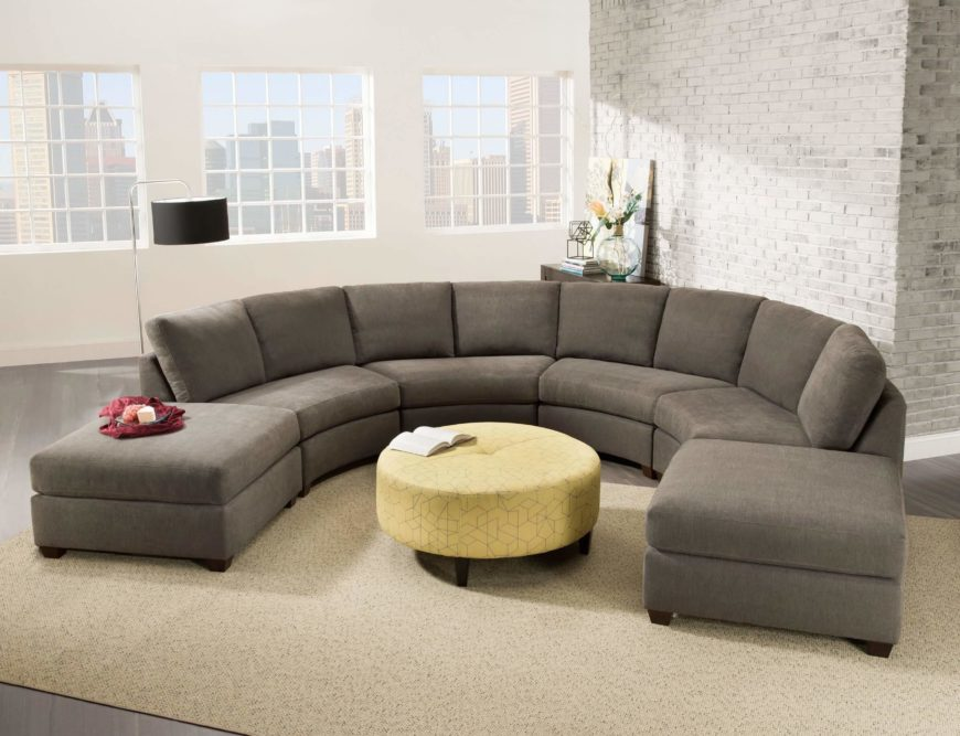 Here's a unique sectional design, crafted in a broad curved U-shape, rather than the standard L-shaped design. This makes for a more striking appearance in virtually any shape room, but especially so in a large man cave with room to spare. A pair of square ottomans bookends the piece.