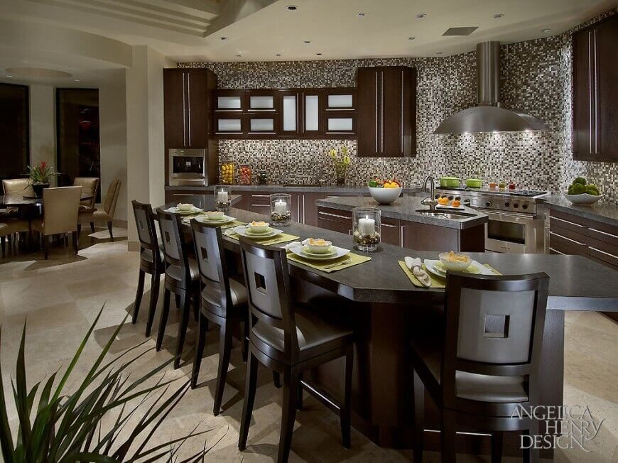 Warm brown cabinets pop against the tile backsplash of this kitchen. Satin finished countertops highlight colors in the busy tile work; as do the stainless steel appliances and accents. Sleek lines complete this contemporary design.