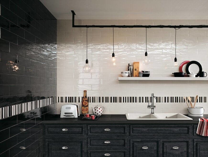 Rustic meets industrial in this monochromatic kitchen with touches of bright red. The weathered counters bring the country while the stark subway tiles and simple hanging lights bring the rock n' roll. A band of narrow tiles breaks up the space and adds some visual interest.