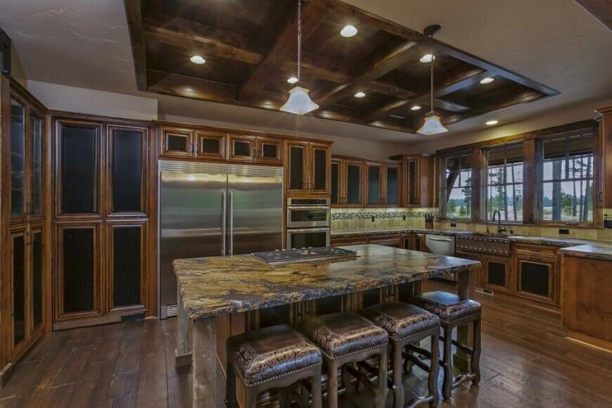 Black cabinet fronts highlight the honey tones of the wood accents in this stunning kitchen. When viewed with the granite slabs of countertop the cabinets bring out the golden accents in the stone. The coffered ceiling creates an interesting visual against the light colored ceiling.