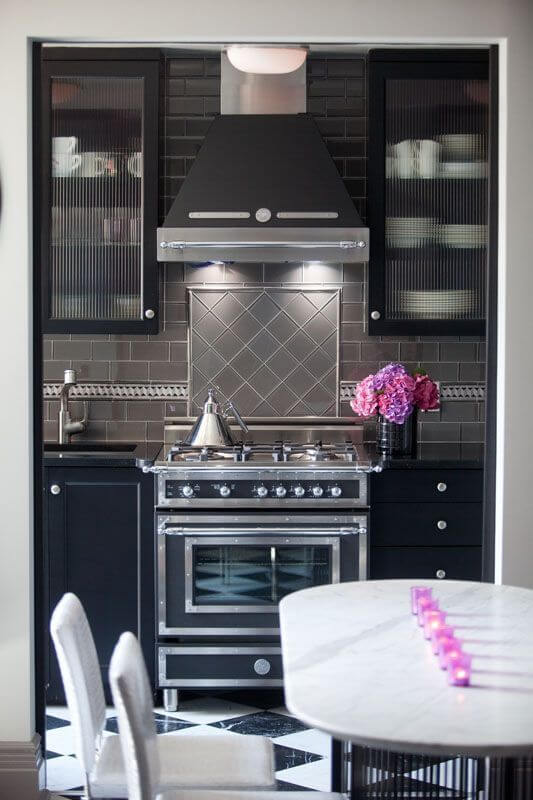 This striking design is a gorgeous combination of shades and textures, keeping to the theme of black, grey, and white. Glass cabinet fronts show hints of white dishes against the black of the cabinets. Grey glass subway tiles create a lighter backdrop for the centerpiece of the room - the marvelous stove.