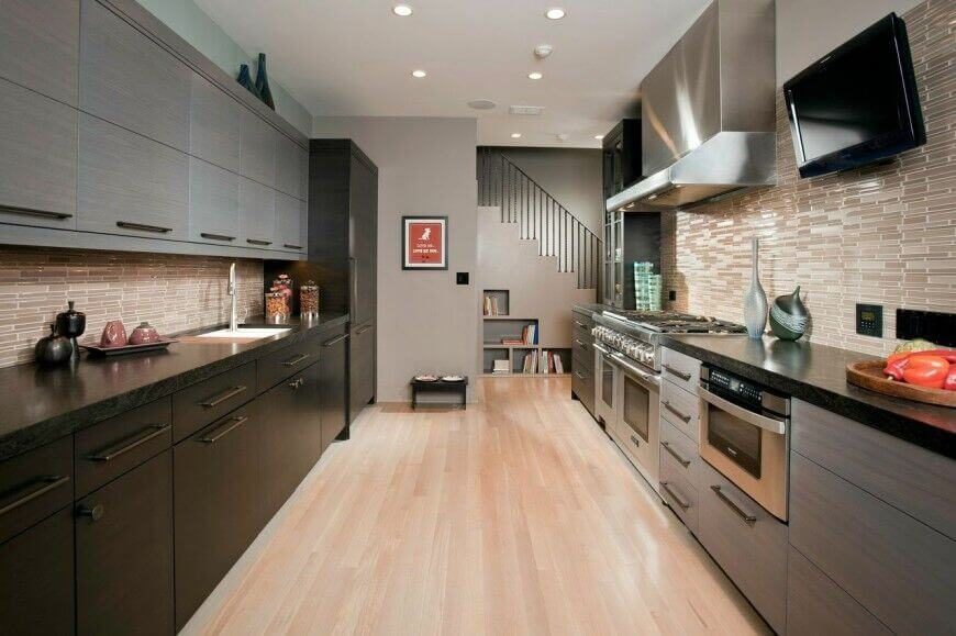 Shades of tan, gray, and black create a lovely palette for this kitchen. Sleek lines and low profile cabinets bring a modern contemporary look to the design. The pale walls and floor offset the dark cabinet colors and keep the room from feeling cave-like