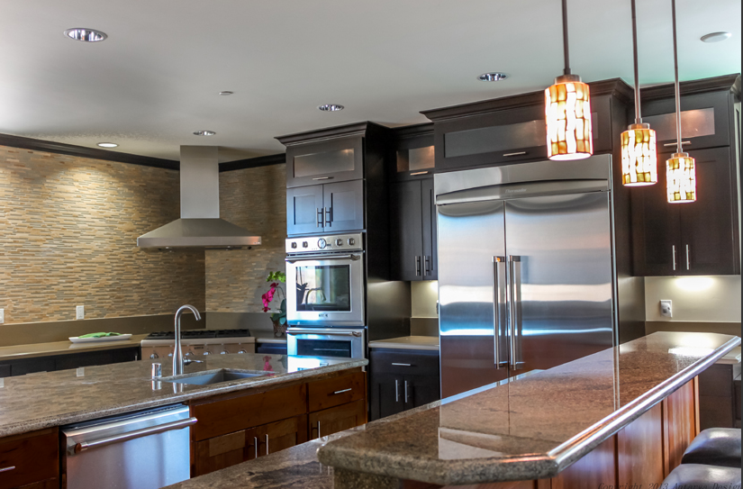 Dark cabinets highlight the granite counters - a mix of black, gray and tan - bringing together the design of the room. A variegated stone backsplash combines the tan and grey to create a striking visual interest along the walls. Stainless steel appliances offset the darker cabinets used against the far wall.