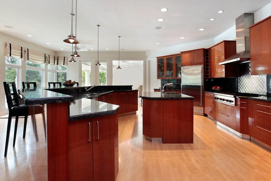 """The bold red color of these cabinets is quite striking against the black granite countertops. The """"quilted"""" stainless steel backsplash behind the stovetop helps reflect light into the room and add to the silver accents used throughout the kitchen."""