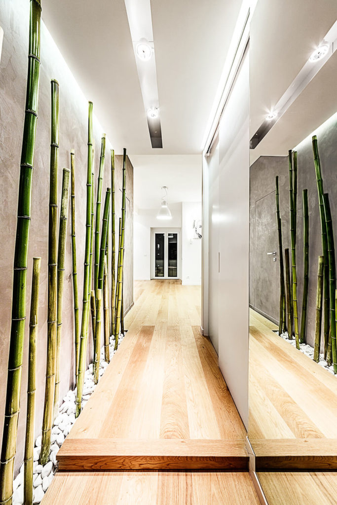 The entry hall introduces the hardwood flooring that informs the entire apartment, flanked by pristine white walls decorated with a slim bamboo forest and a massive mirror. The intricate recessed lighting highlights the length of the bamboo, nested into white stones at the floor.