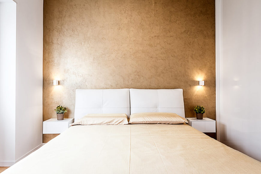 In the master bedroom, we see the gold accent wall backing the light hued bed, flanked by a pair of floating bedside tables in white. Bespoke wall sconces glow sympathetically beside the white pillow headboard.
