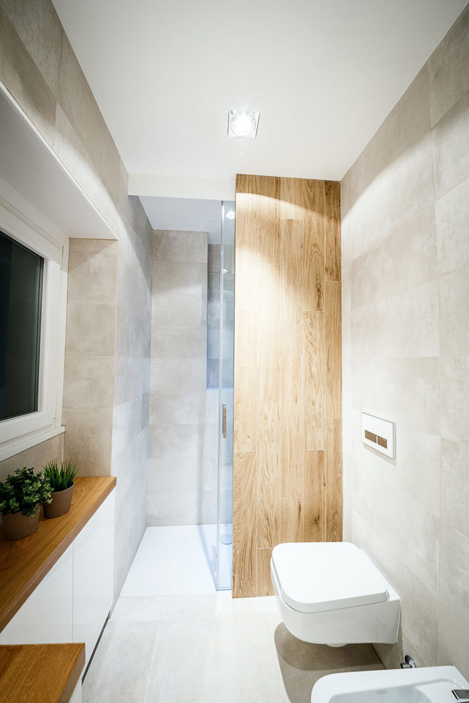 The large glass enclosed, walk-in shower is partially obscured by a rich oak panel, helping divide this larger bathroom into segments.