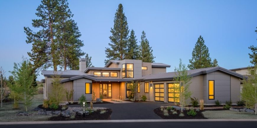Viewing the home on approach, we can see the intricately placed windows dotting the complex, textured exterior. The singular neutral color palette anchors the modern structure.